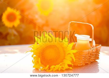 Sunwlower and jug with oil in a wicker basket. backlight blurred