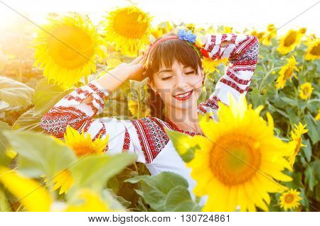 Pretty young woman in national ukrainian blouse embrodery with closrd eyes on a sunflower plant at sunset backlight.