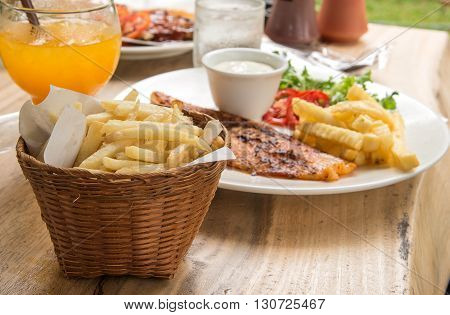 Fish steak in White plate Glass of water French fries Orange juice placed on wooden table.