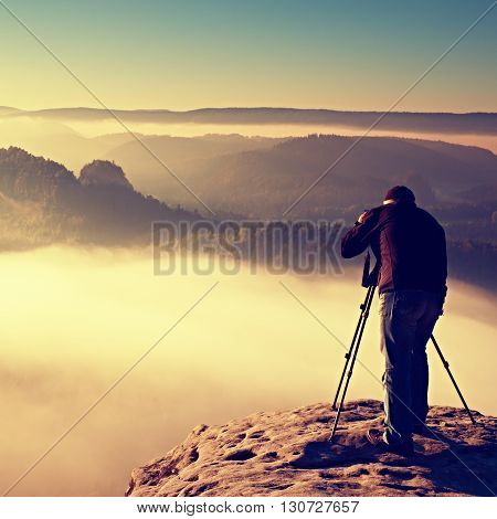 Professional On Cliff. Nature Photographer Takes Photos With Mirror Camera On Rock. Dreamy Fogy Land