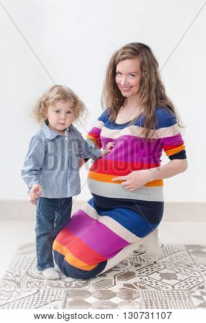 Young pregnant woman in colorful clothing tells her elder child that baby will be born soon pointing to her belly both looking at the camera and smiling