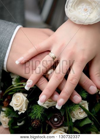 wedding shoot of a golden ring and hands