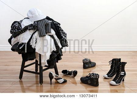 Montón de ropa en un taburete y zapatos desordenados