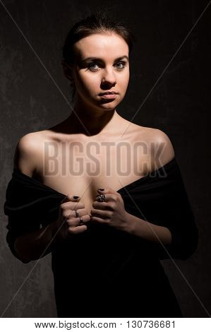 fashion caucasian beautiful woman low key portait over dark background hands on chest