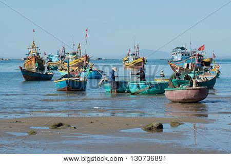 MUI NE, VIETNAM - DECEMBER 25, 2015: Fishermen and fishing boats are preparing to go to sea for night fishing. The fishing harbour of Mui Ne