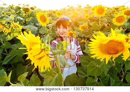 Cute young girl in national ukrainian blouse embrodery looking to camera on a sunflower field at sunset backlight.