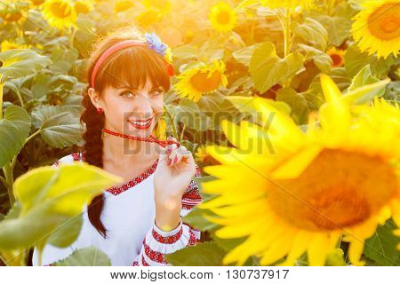 Pretty young girl in traditional ukrainian blouse embrodery looking to camera on a sunflower plant at sunset backlight.