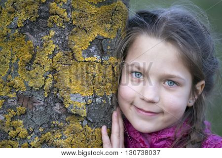 smiling girl portrait close to the mossy tree stem