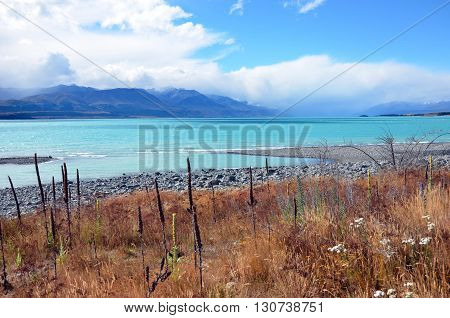 Crystal clear turquoise lake with clouds rolling over mountains in the distance.