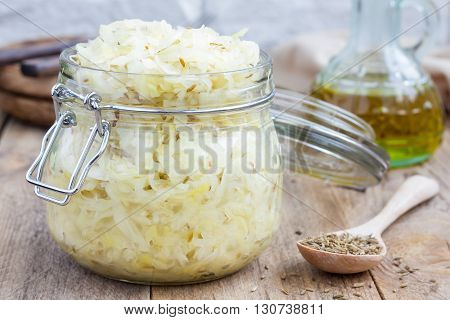 Homemade sauerkraut with cumin in a glass jar, closeup