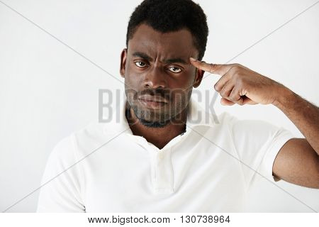 Close Up Portrait Of Angry Young Dark-skinned Businessman Wearing Casual Clothes, Gesturing With Ind