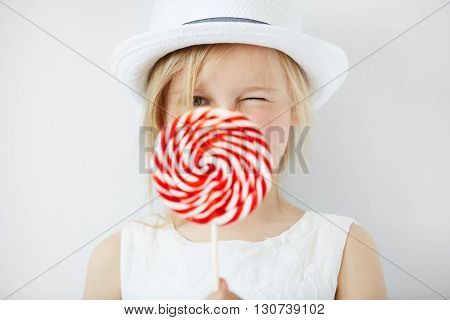 Close Up Portrait Of Beautiful Little Female Child In White Hat Holding Huge Spiral Lollipop, Having