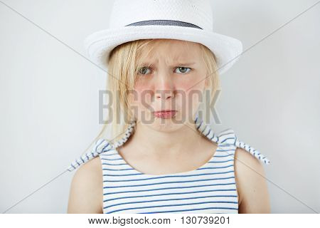 Studio Portrait Of Sad Little Girl In Stylish Clothes Crying And Acting Naughty, Looking At The Came