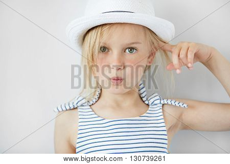 Close Up Shot Of  Annoyed And Angry Girl Wearing White Hat And Striped Dress, Holding Index Finger A