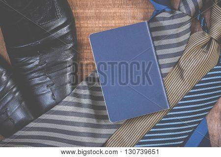 Necktie and shoespassport on grunge wood background