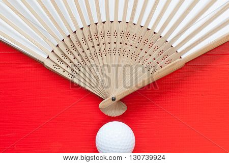 Typical Japanese hand fan made and golf ball on the wooden red table