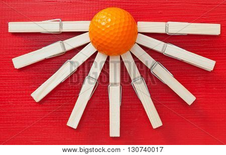 Set of cloth pegs and golf ball on wooden red table