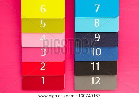 Twelve different color diaries on a pink wooden table