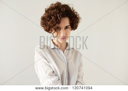 Close Up Of Serious Pretty Caucasian Female With Short Brown Curly Hair Wearing Trendy White Shirt.