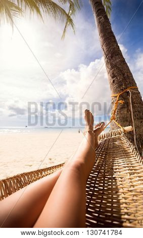 view of nice sexy smooth woman's legs in a hammock on tropical resort