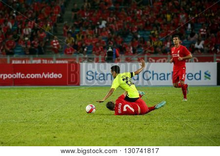 July 24, 2015- Shah Alam, Malaysia: Liverpool's James Milner (7) and Malaysia's M. Nasir (20) challenges for the ball in the friendly match. Liverpool Football Club from England is on an Asia tour.