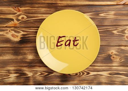 Yellow plate on a brown wooden table, eat