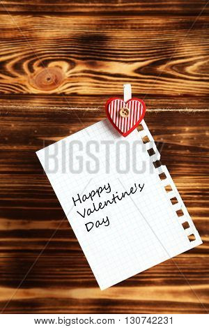 Blank paper hanging on rope on brown wooden background, happy valentine's day