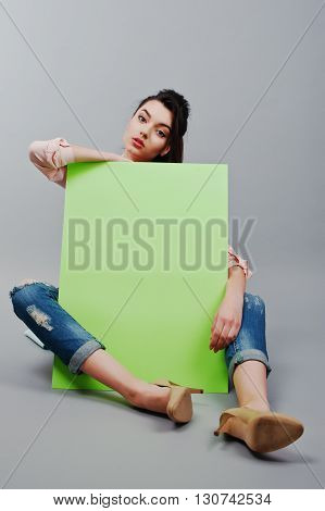 Full Length Of Beautiful Girl Sitting, Holding Green Blank Advertising Board Banner, Over Gray Backg
