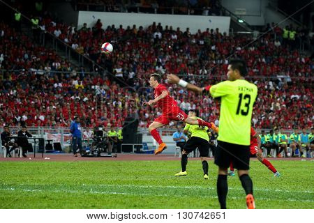July 24, 2015- Shah Alam, Malaysia: Liverpool's Lucas Leiva (red) heads the ball in a friendly match against the Malaysian Team. Liverpool Football Club from England is on an Asia tour.