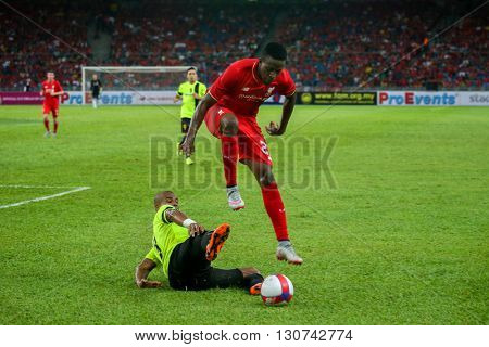 July 24, 2015- Shah Alam, Malaysia: Liverpool's Dovock Origi (red) dribbles the ball in a friendly match against the Malaysian Team. Liverpool Football Club from England is on an Asia tour.