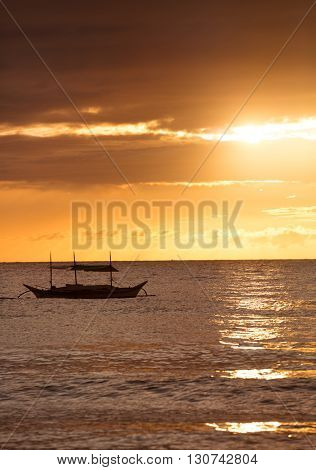 Silhouette of fish boat over dramatic sky, sunset
