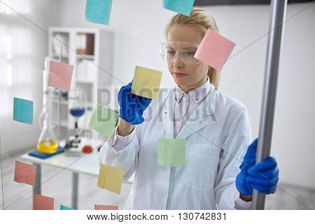 Woman scientist in laboratory write chemical formula on sticky notes