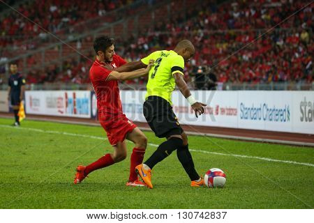 July 24, 2015- Shah Alam, Malaysia: Liverpool's Adam Lallana (red) challenges Thiago (green) for the ball in a friendly match against Malaysia. Liverpool Football Club from England is on an Asia tour.