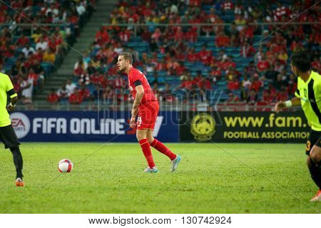 July 24, 2015- Shah Alam, Malaysia: Liverpool's Jordan Henderson (red) dribbles the ball in a friendly match against the Malaysian team. Liverpool Football Club from England is on an Asia tour.