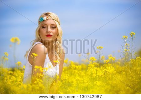 Dreaming woman with closed eyes in blooming field