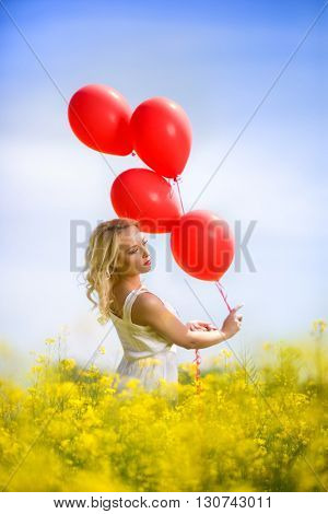 Attractive girl standing in yellow flowers with balloons
