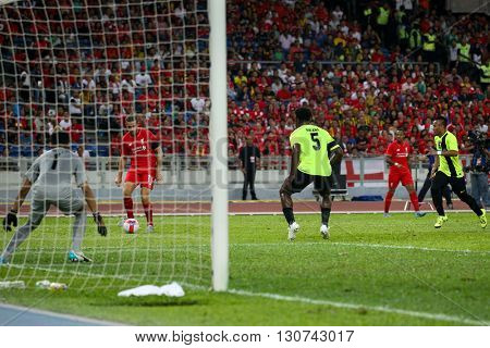 July 24, 2015- Shah Alam, Malaysia: Liverpool's Jordan Henderson (red) shoots at goal in a friendly match against the Malaysian team. Liverpool Football Club from England is on an Asia tour.