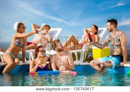 Guys and girls refreshes on swimming pool with cold drinks at summer
