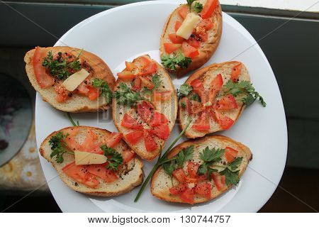 appetizing light vegetarian snack from bread and tomato, verdure and cheese on plate in shape of flower