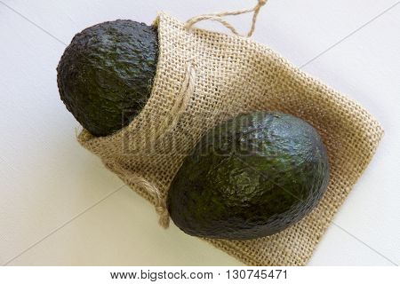 Two ripe avocados with a hessian bag.