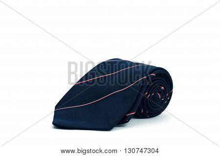 Roll of dark blue tie on a white background. Necktie on white background.