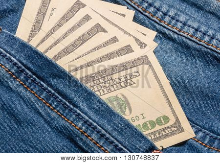 American dollar bills in jeans pocket background. Dollars in a jeans pocket
