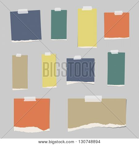 Colorful ripped blank note paper are stuck on gray background.