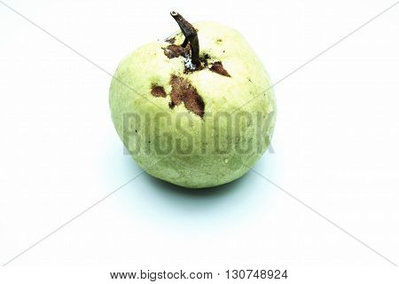 Guava fruit with brown marks, isolated on white background.