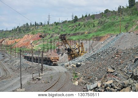 Excavator loading the iron ore to the cargo train on the opencast