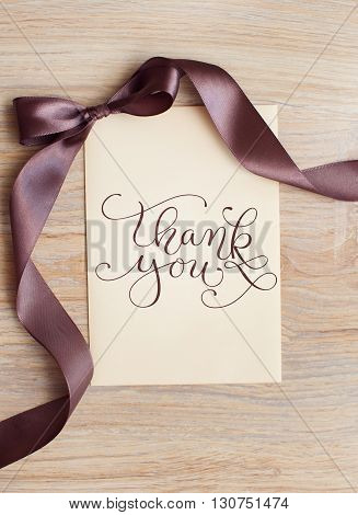 close up of card note with brown ribbon and words thank you.