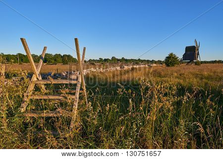 Alvar limestone moor with fence and old windmill in sunset at Isle if Oeland province Kalmar Sweden