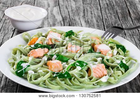 Salmon and Spinach Fettuccine pasta on white dish cream sauce in a gravy boat on dark wooden table italian style studio lights side view close-up