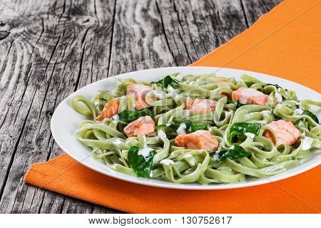 Salmon and Spinach Fettuccine alfredo pasta on white dishes and orange table napkin on a rustic table italian style studio lights close-up