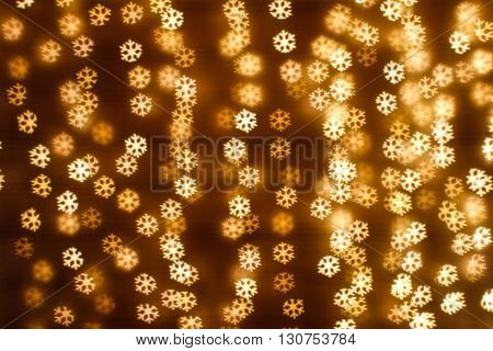 Blurring lights bokeh background of golden snowflakes